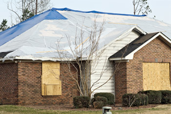 House board up and tarping after a tornado
